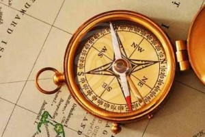 antique-brass-compass-over-old-canadian-map-2